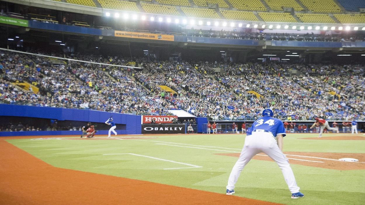L'instructeur du premier but des Blue Jays regarde attentivement le lanceur et le frappeur s'élancer lors du match du 26 mars au stade olympique.