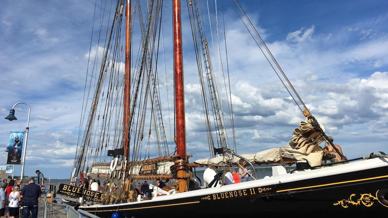 La réplique du légendaire Bluenose, accosté, avec des visiteurs à bord.