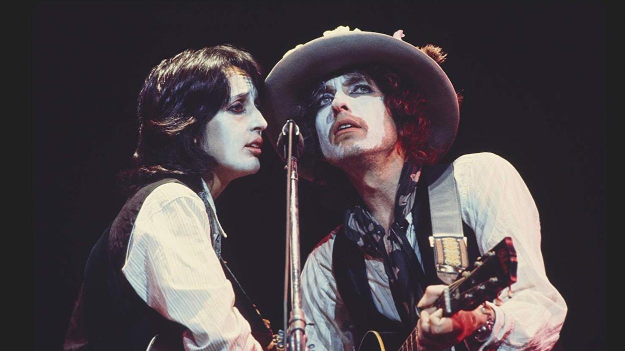 Une chanteuse et un chanteur sont sur scène devant un micro, guitare à la main. Ils ont le visage couvert de maquillage blanc.