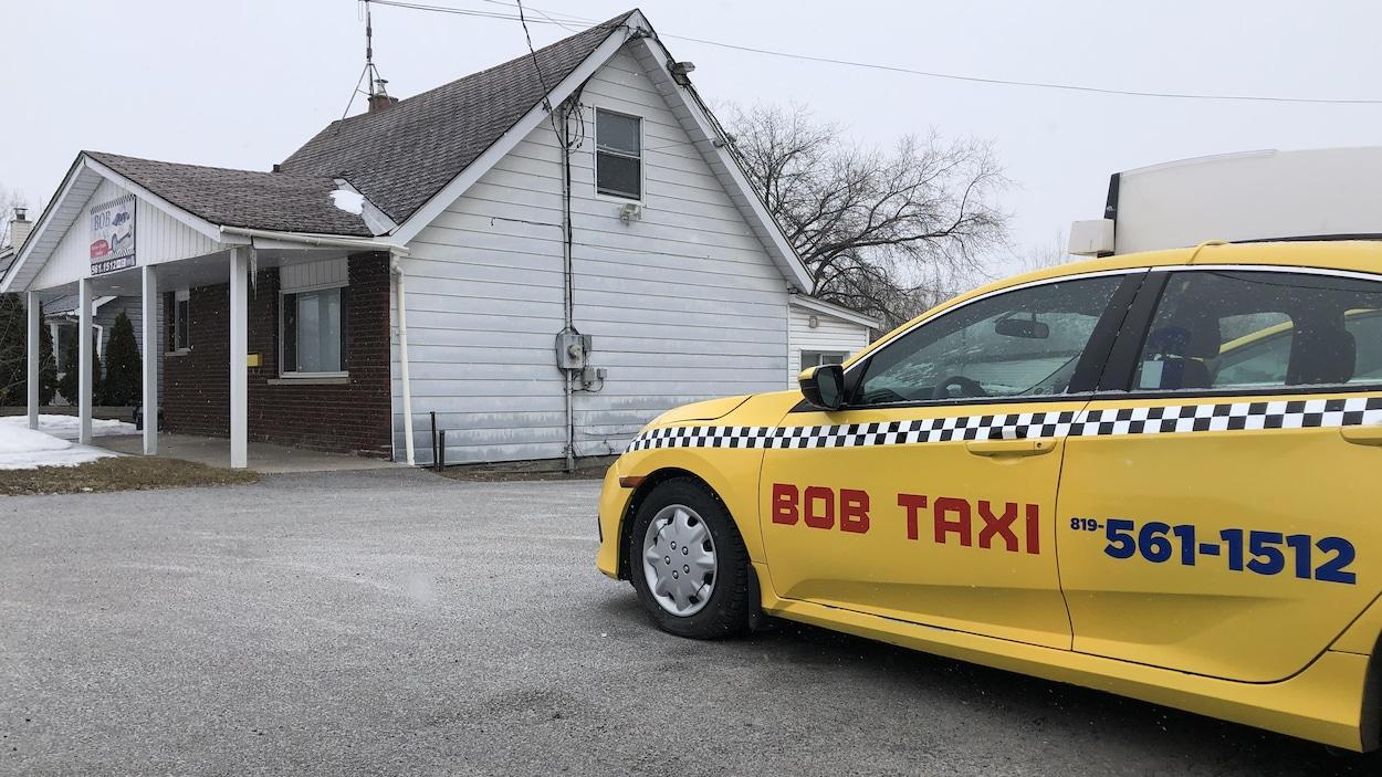 Une voiture de taxi dans un stationnement, en hiver.