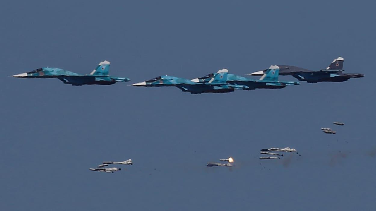 Des avions Sukhoi Su-34 russes larguent des bombes lors de manoeuvres aériennes.