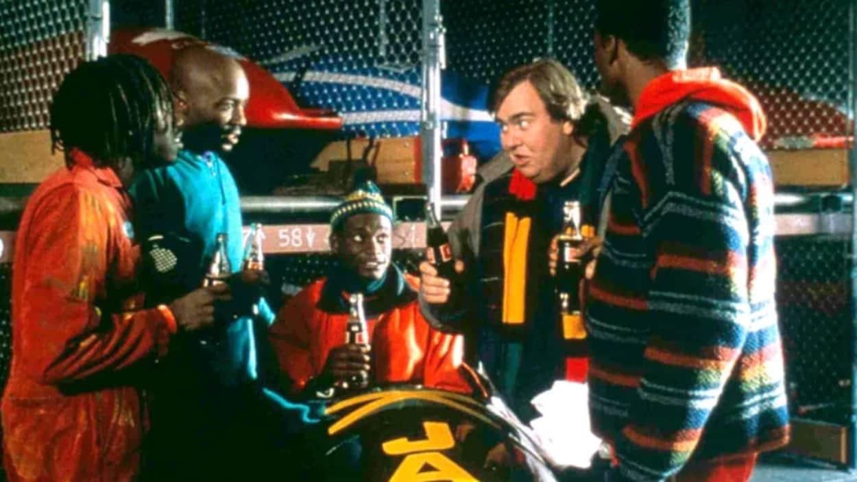 Un acteur est dans un bobsleigh et quatre autres sont autour de lui. Ils tiennent chacun une bouteille de Coca Cola.