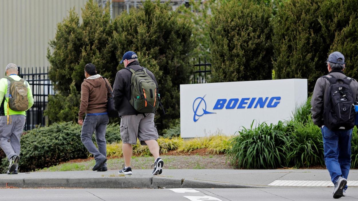 Des personnes de dos se dirigent vers l'entrée d'une usine de Boeing.
