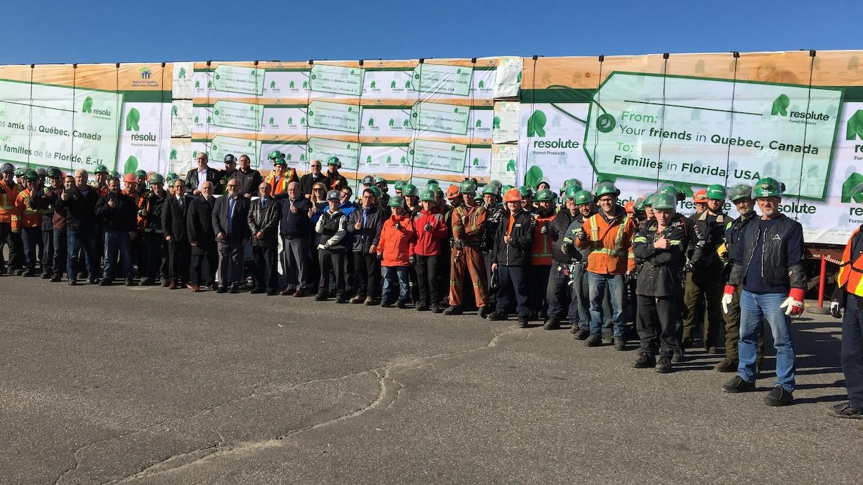 Employés, cadres et personnalités politiques sont photographiés devant le convoi ferroviaire de bois envoyé par Produits forestiers Résolu aux populations du sud des États-Unis touchées par les ouragans.