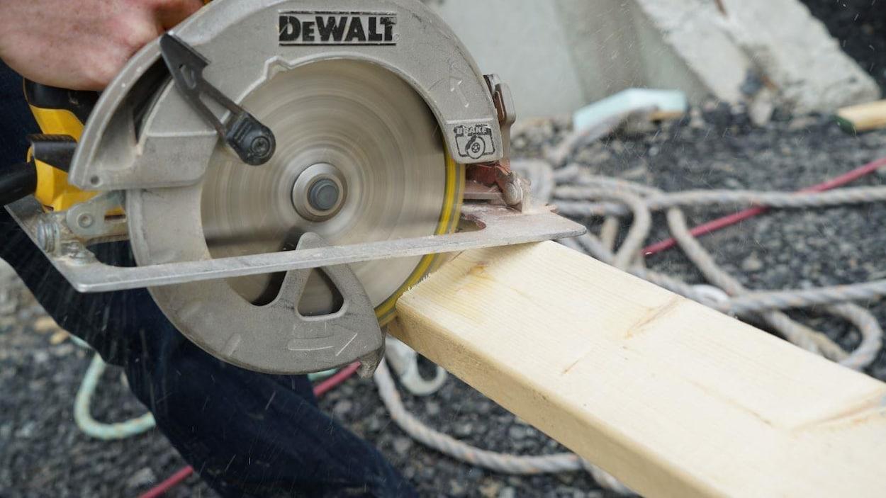 Un travailleur de la construction scie une planche de bois.
