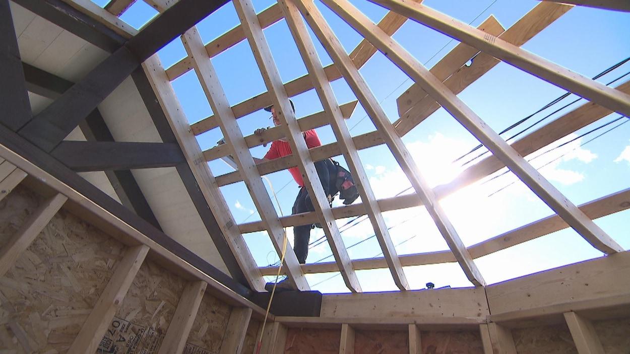 Un homme construit une structure de bois.
