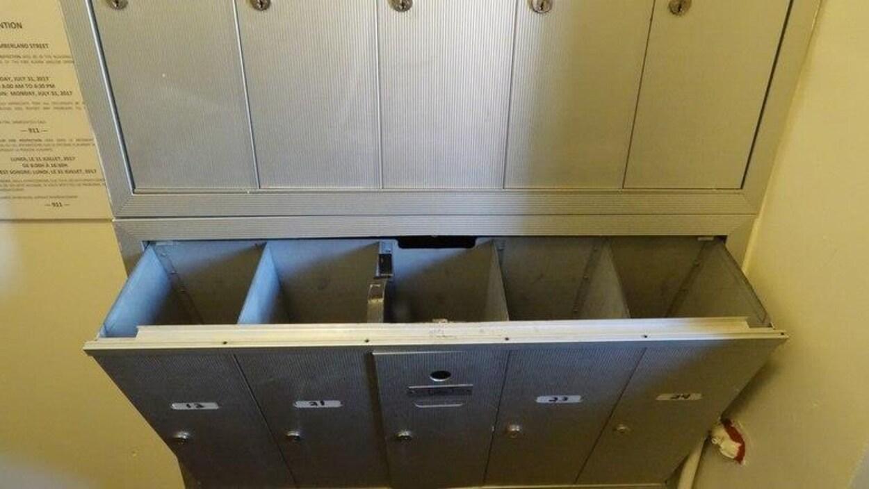 Une unité de boîtes aux lettres ouvertes dans le hall d'un immeuble.