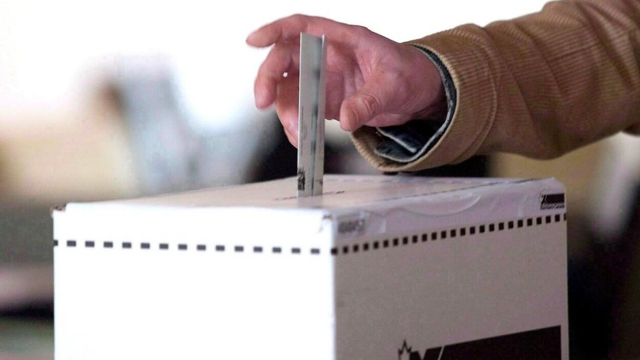 Une main qui dépose un bulletin de vote dans une boîte de scrutin.