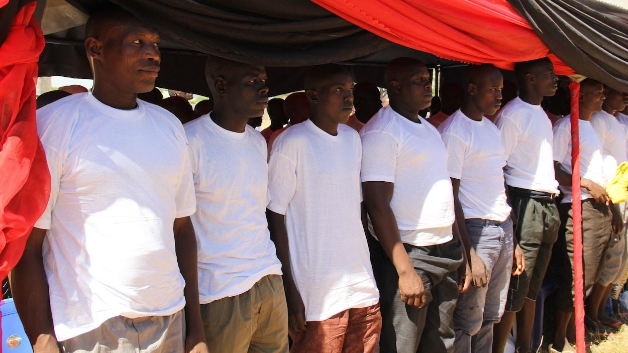 Des hommes portant tous des chandails blancs sont debout en rangée.