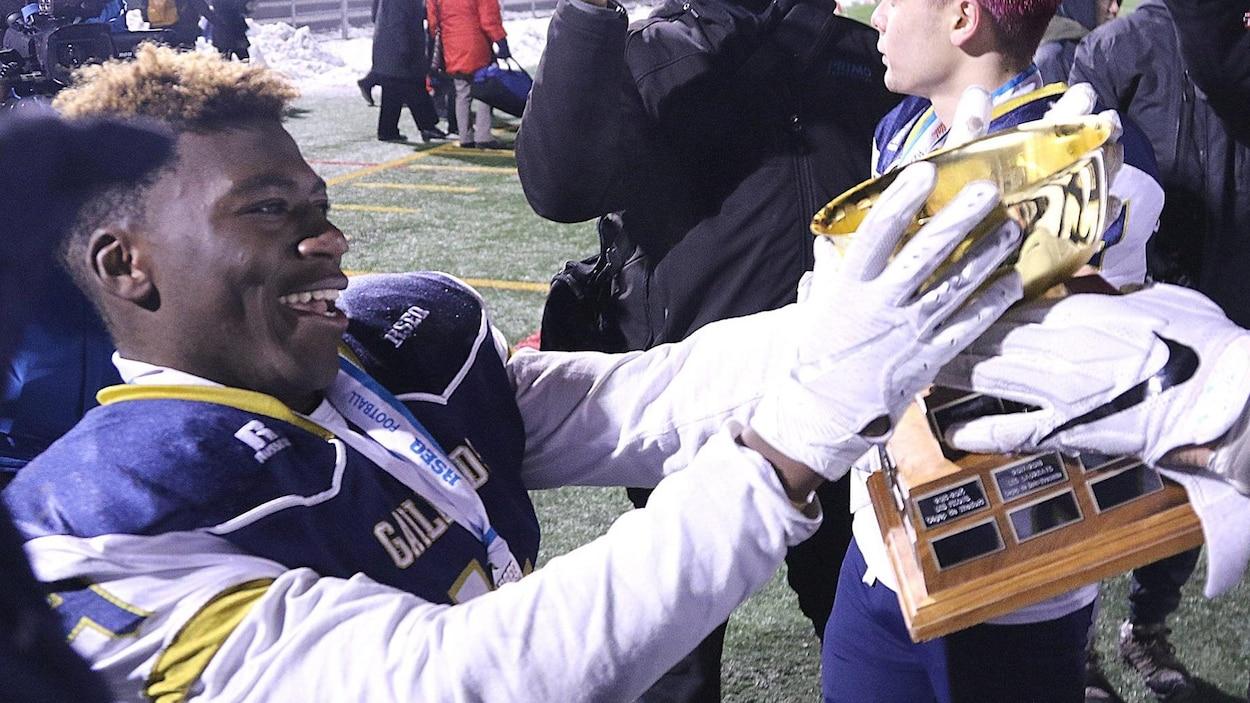 Un joueur des Gaillards prend le trophée dans ses mains.