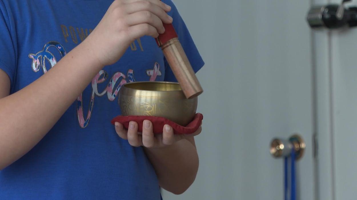 Un enfant pratique un rituel de méditation à l'aide d'un bol tibétain.