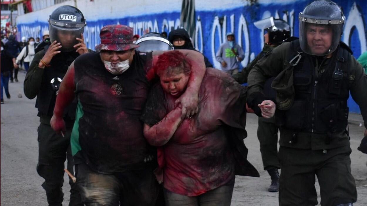 Patricia Arce couverte de peinture rouge escortée par des policiers.