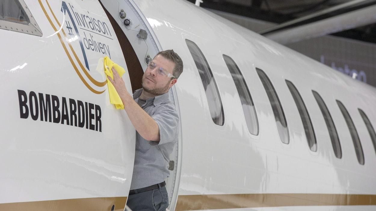 Un homme passe un linge sur la carlingue d'un avion.