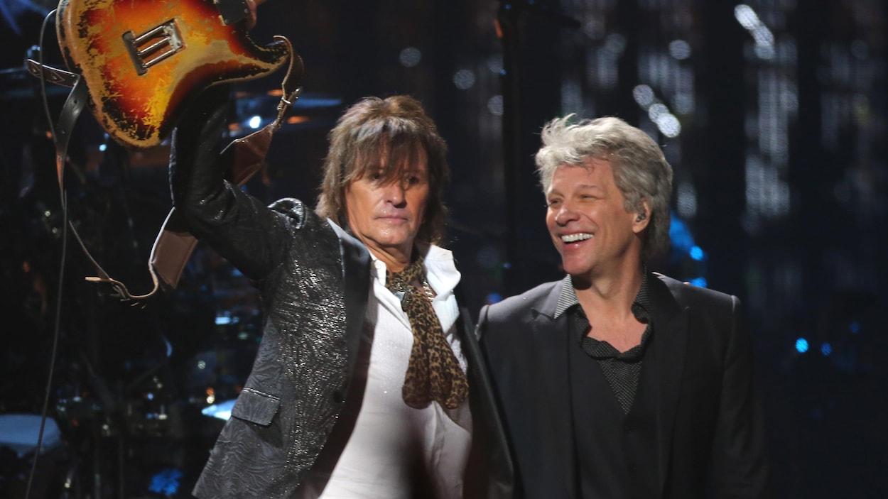 Le guitariste Richie Sambora lève sa guitare dans les airs alors qu'il fait l'accolade au chanteur Jon Bon Jovi sur scène lors de la cérémonie d'intronisation.
