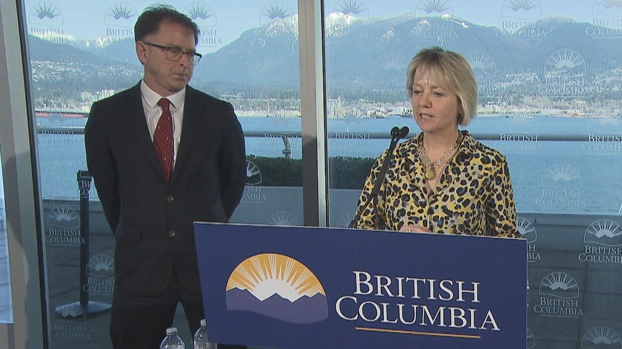 Le ministre de la Santé, Adrian Dix, et la médecin hygiéniste en chef, Bonnie Henry debout devant deux micros en point de presse le 14 mars 2020.