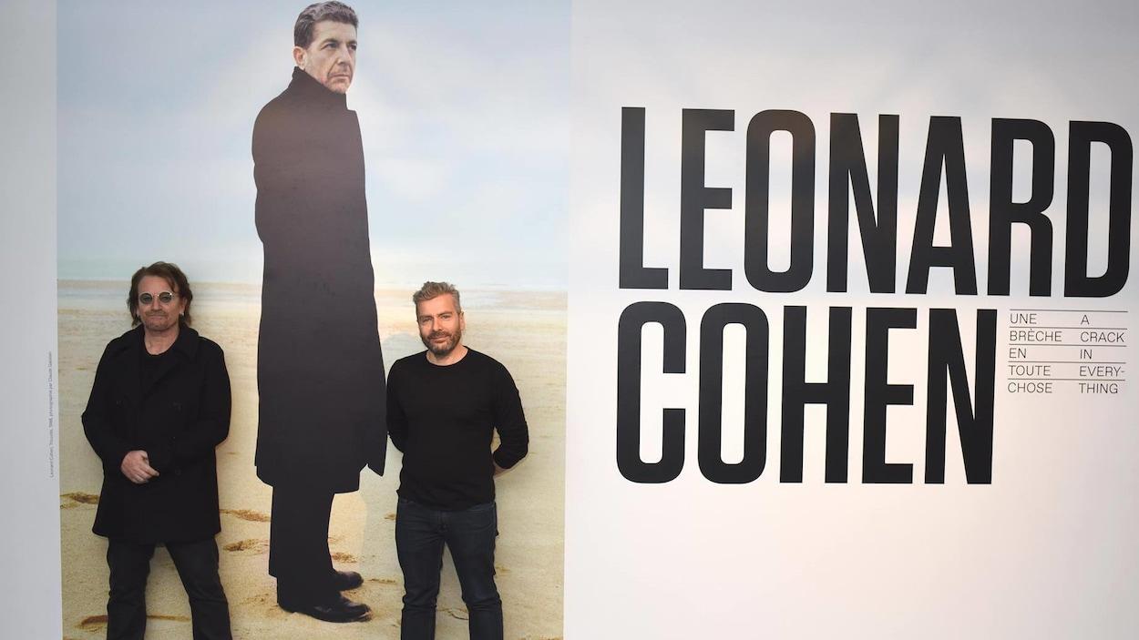 Les deux hommes posent devant une photo géante de Leonard Cohen,