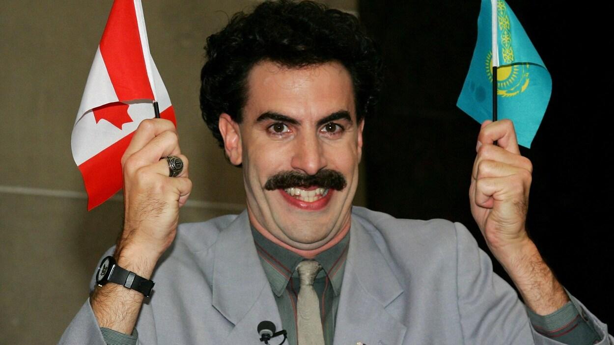 Un homme ayant une épaisse moustache tient un drapeau du Canada et un drapeau du Kazakhstan dans ses mains en souriant.