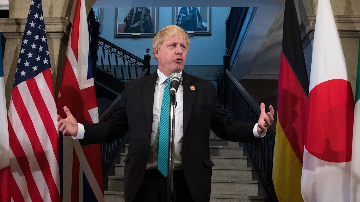 Boris Johnson, debout devant un micro.