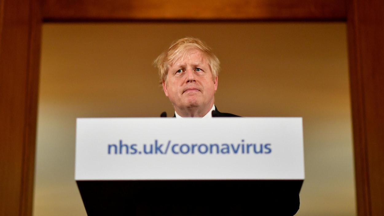Un homme derrière une tribune sur laquelle est écrit : coronavirus.