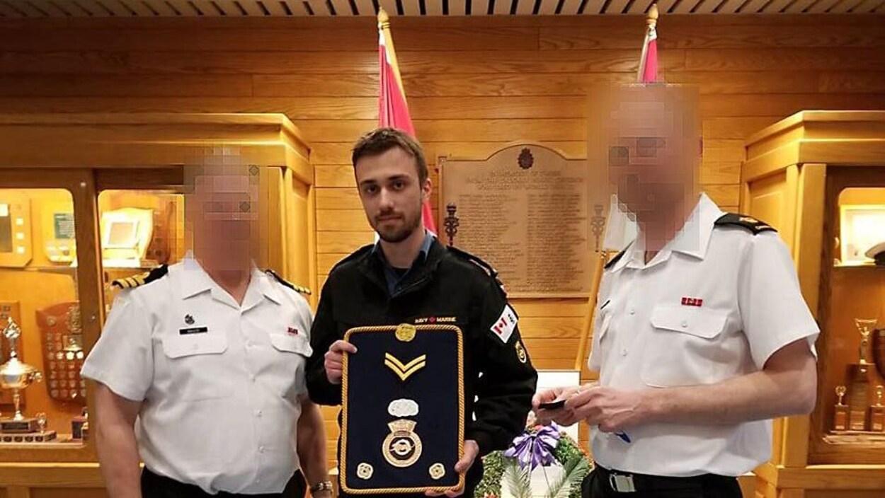 Un jeune homme en uniforme, entre deux officiers, tient une enseigne militaire.