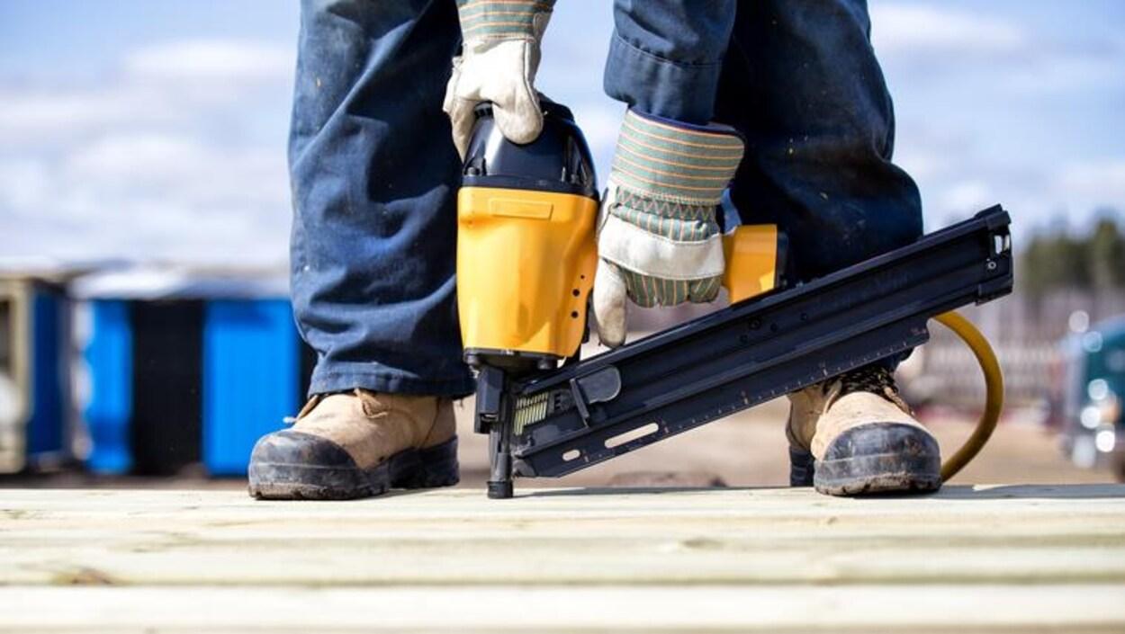 Une personne cloue avec des bottes et des gants de sécurité.