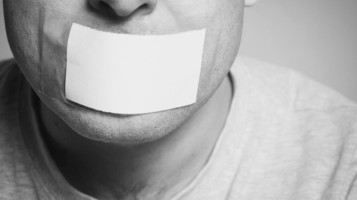 Un homme dont la bouche est masquée par un bout de papier collé à la peau.