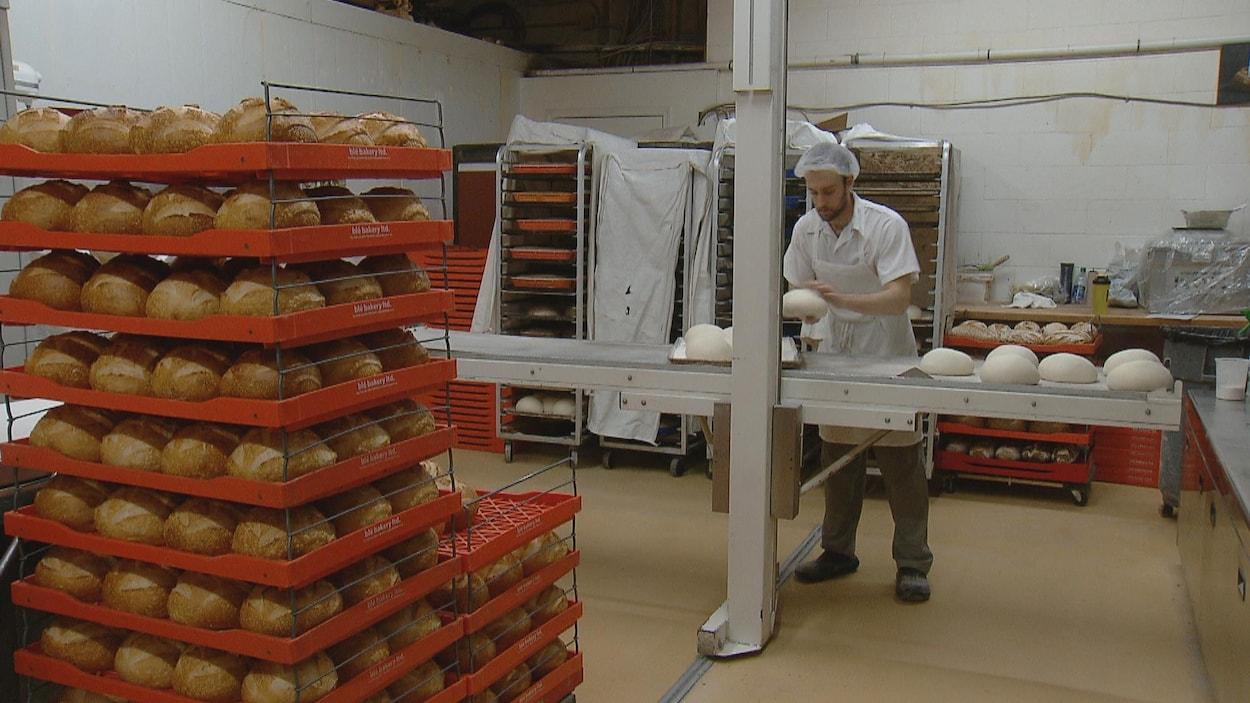 Un homme en uniforme de chef façonne de la farine sur un comptoir alors que des miches cuites reposent sur des barquettes.