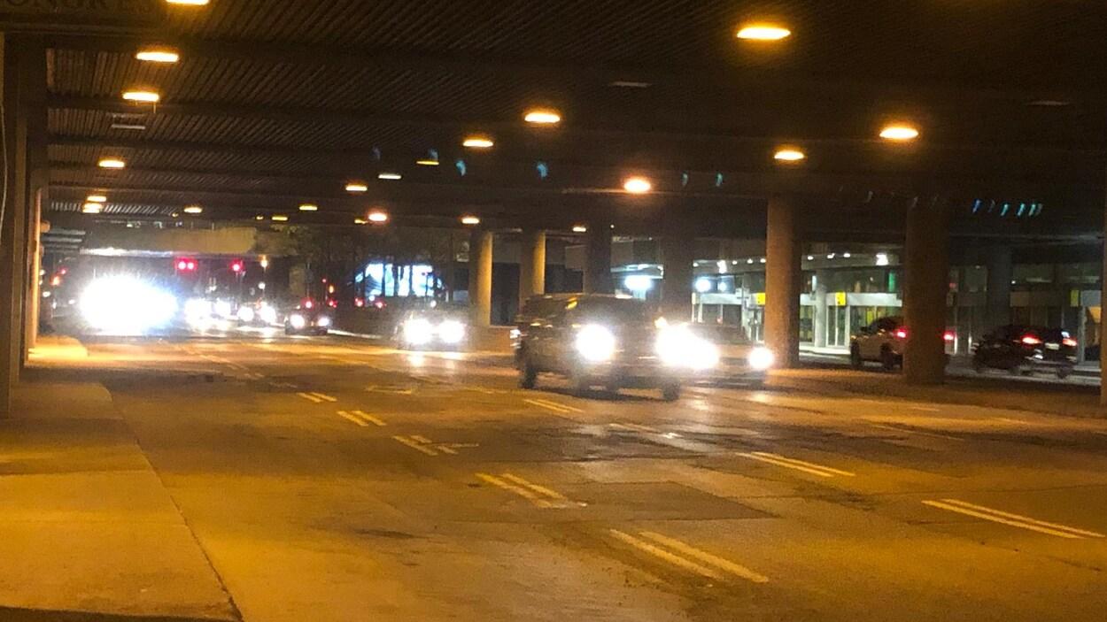 Des voitures sous la poutre du boulevard Maisonneuve, en soirée.
