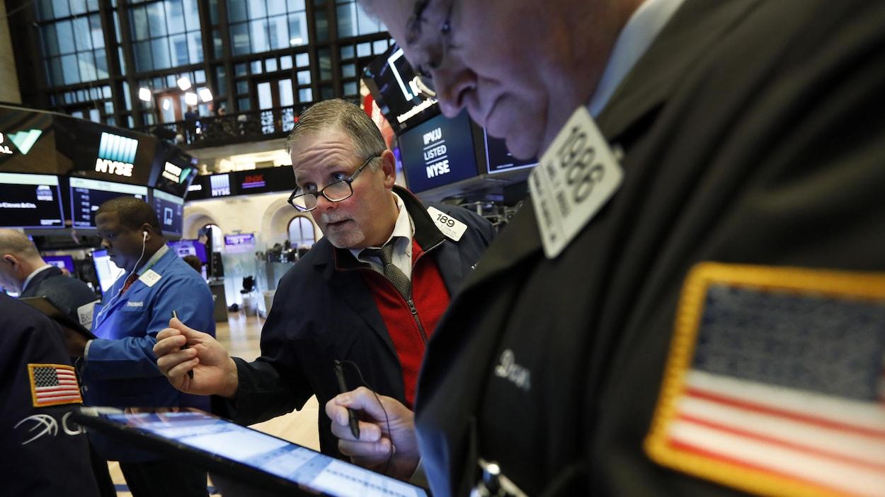 Des employés de la Bourse à New York s'affairent, la mine soucieuse.