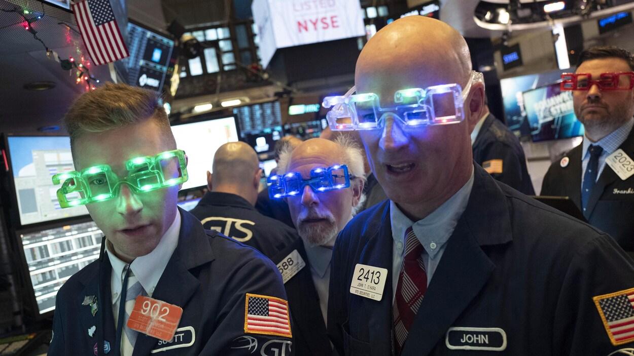 Quatre hommes portent des lunettes lumineuses affichant « 2020 » à la bourse de New York.