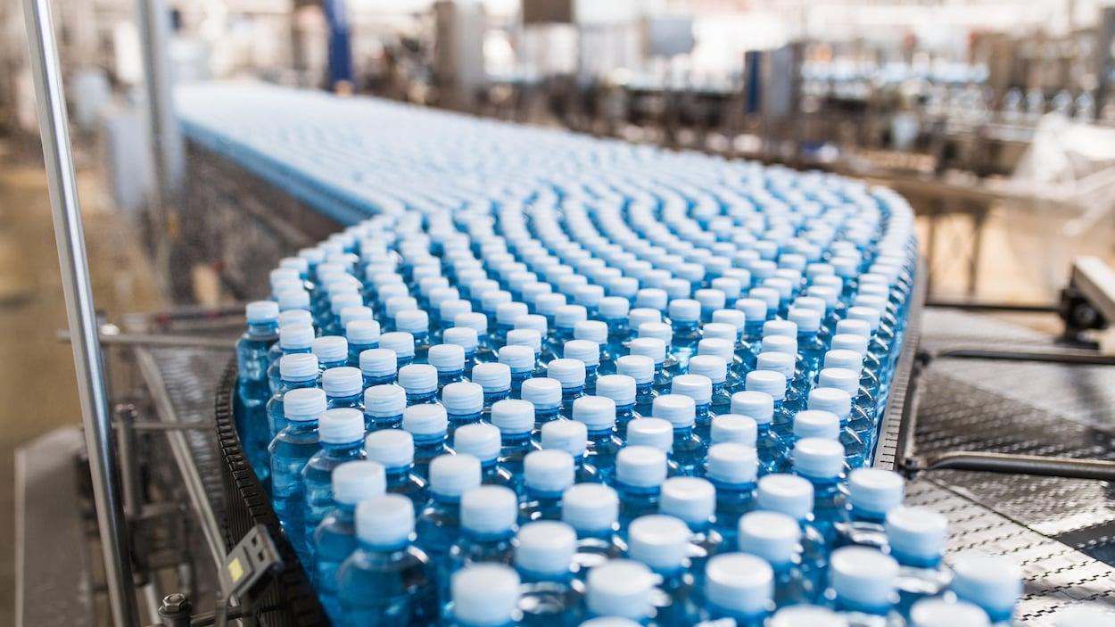 Des bouteilles de plastique dans un convoyeur.
