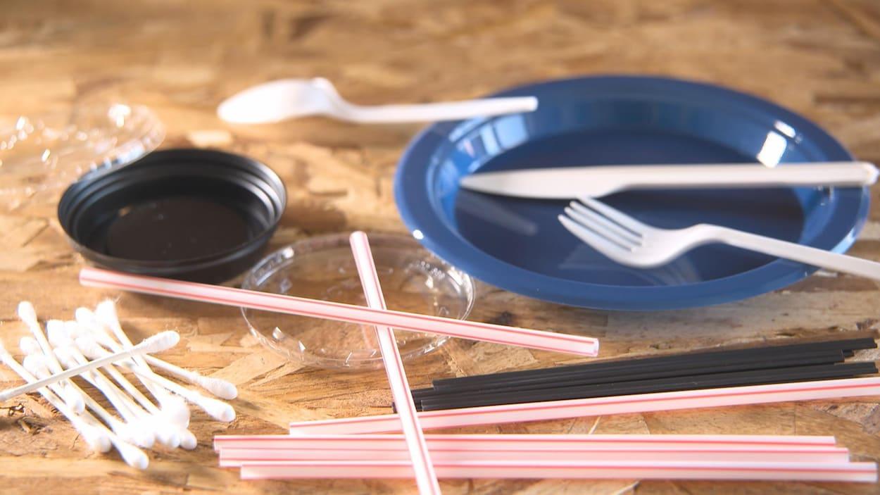 Des pailles et des ustensiles de plastique sur une table