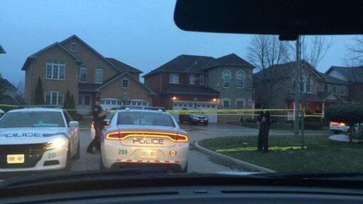 Un policier derrière un véhicule tient son arme de service.