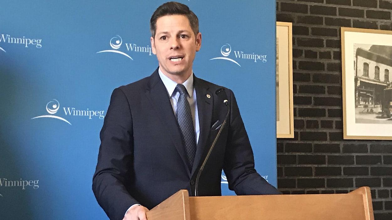 Brian Bowman, maire de Winnipeg, fait une allocution debout devant un lutrin.