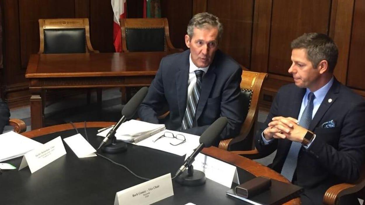 Deux hommes dans un bureau, devant une table sur laquelle sont posés des micros.