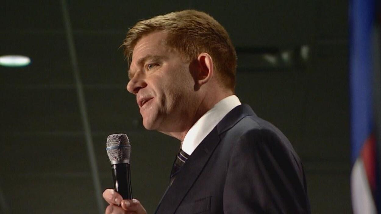 Le candidat à la direction du Parti conservateur uni Brian Jean au micro pendant un débat l'opposant à Jason Kenney et à Doug Schweitzer