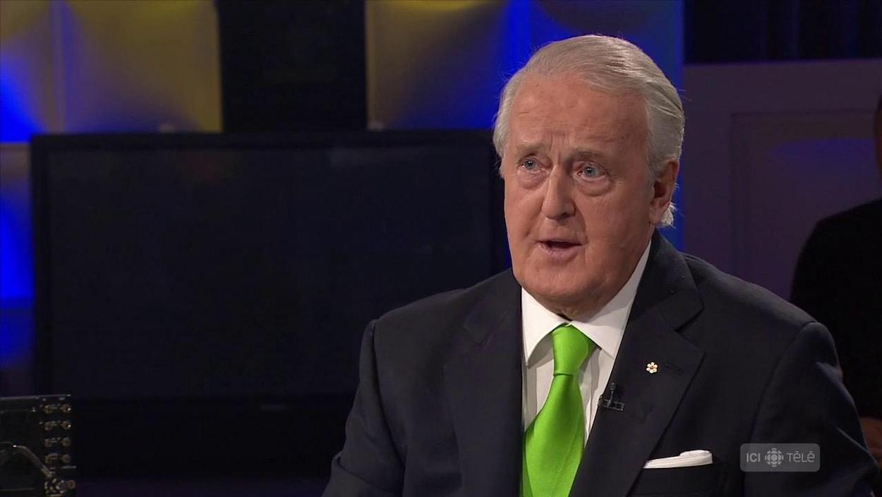 Un homme avec une cravate verte et un veston.