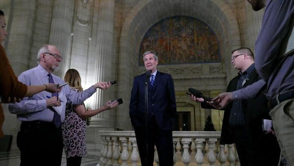 Brian Pallister, entouré de journalistes lors d'une mêlée de presse.