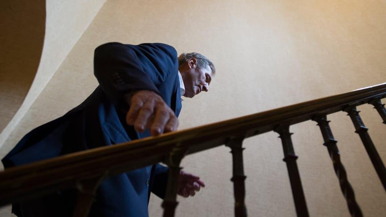 Un homme montant les marches d'un escalier, vu en contre-plongée.