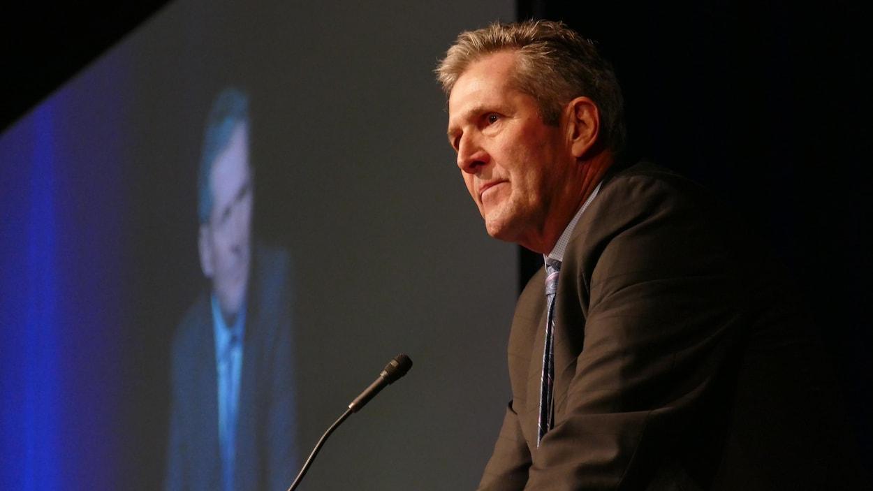 Brian Pallister, vu de profil, devant un micro dans une salle sombre. En arrière-plan derrière lui, on voit un écran géant qui projette son image.