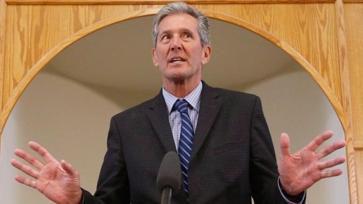 Brian Pallister, en costume cravate, lève les mains devant un micro, l'air surpris.