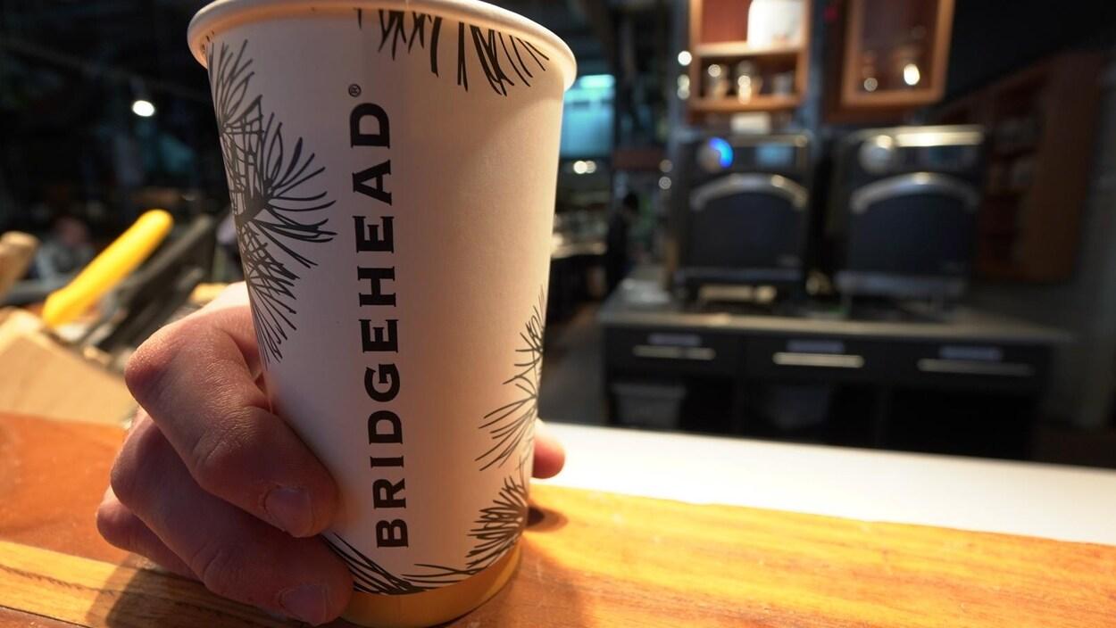 Une main tient une tasse de café en carton de la marque Bridgehead.