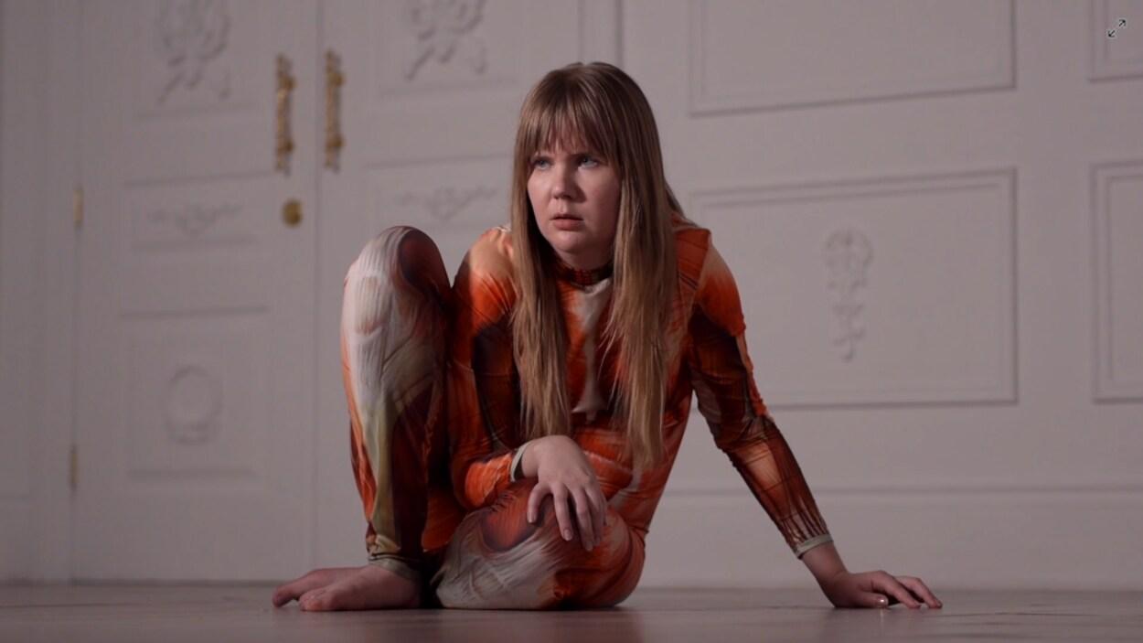 L'artiste Bridget Moser accroupie au sol, vêtue d'un juste au corps qui représente la structure musculaire humaine.