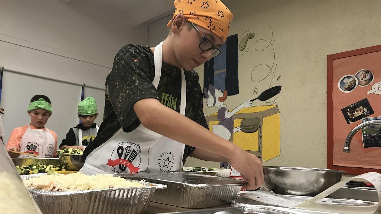 Un jeune homme ferme le couvercle d'une lasagne dans un plat en aluminium.