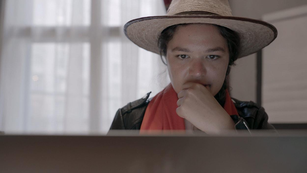Une femme regarde attentivement l'écran de son ordinateur