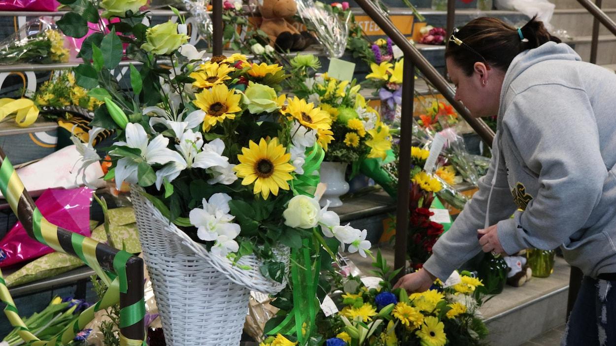 Une femme dépose des fleurs. Elle porte un chandail blanc.