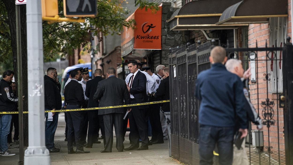 Des policiers en uniforme et des enquêteurs derrière un ruban de scène de crime devant un commerce.