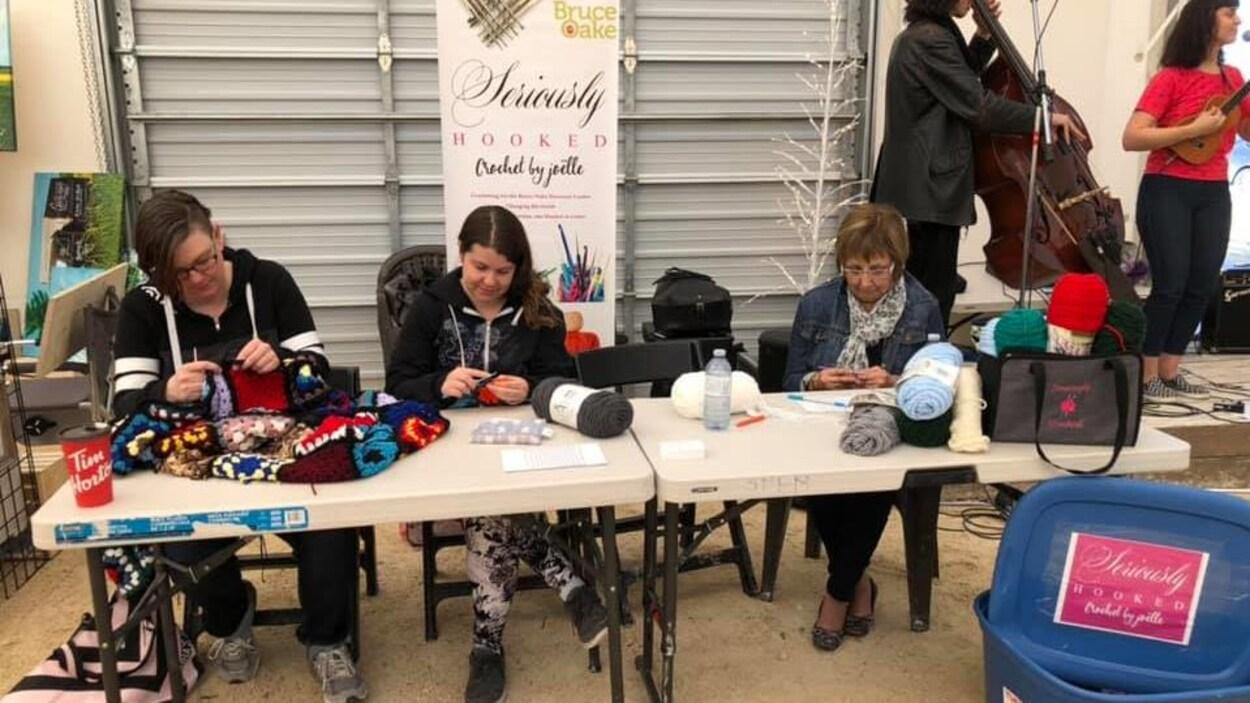 Trois femmes sont installées à une table dans un marché et crochètent.