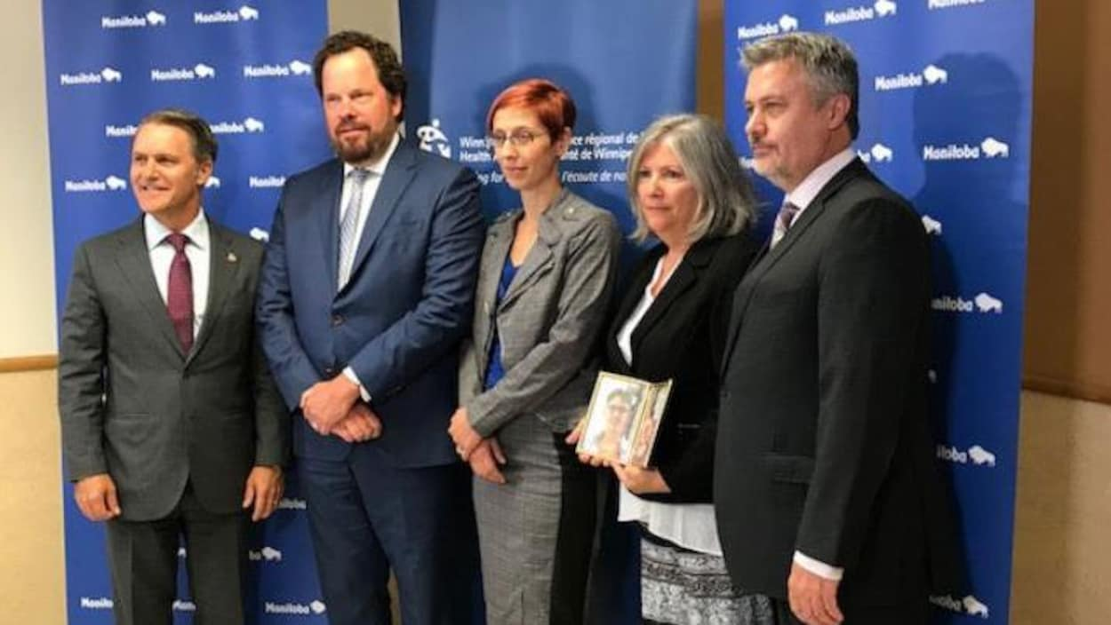 Cinq personnes sont debout et posent pour une photo. Le Dr Bruce Roe est le deuxième à partir de la gauche. Il porte un habit et croise les mains devant lui.