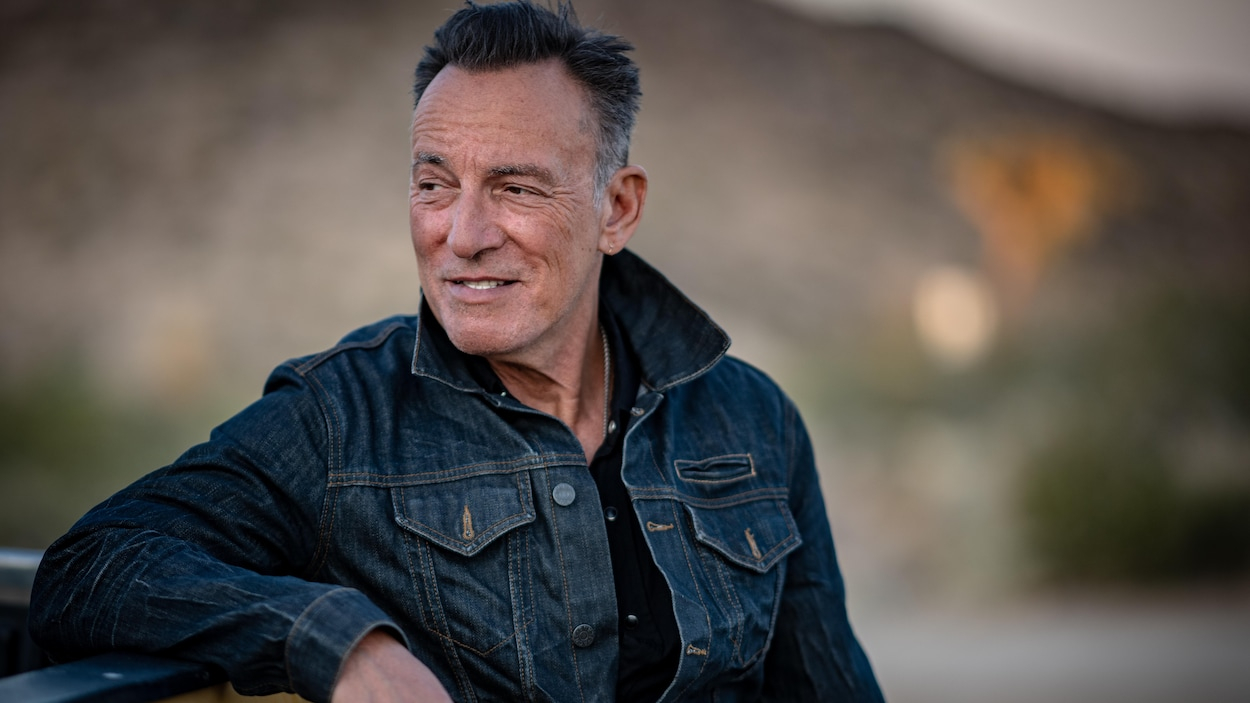 Bruce Springsteen sourit en regardant au loin.